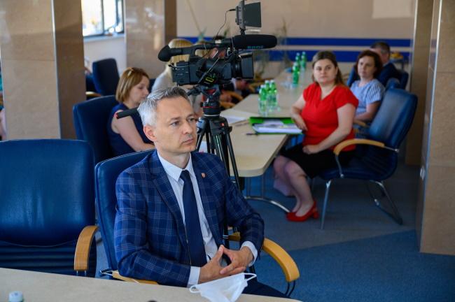 Tomasz Stelmach słuchający przemowy, w tle uczestnicy spotkania