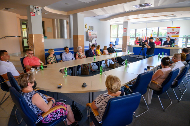Widok z oddali na uczestników siedzących przy okrągłym stole